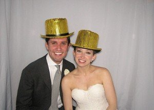 bride & groom in gold hats with white backdrop